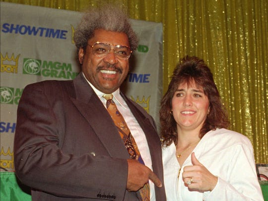 Women's lightweight boxer Christy Salters, right, strikes a pose with boxing promoter Don King during a news conference Thursday, Feb. 8, 1996, at the MGM Grand Hotel in Las Vegas. Salters became the first female professional boxer to be seen live on U.S. premium television when she fought Sue Chase on SHOWTIME from the MGM Grand.