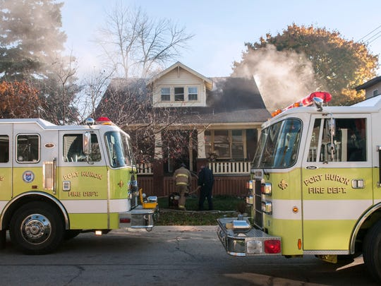 Two firefighters start a fan to vent the house as they