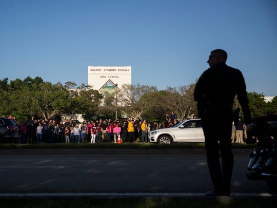 A police officer helps direct traffic Wednesday, Feb. 28, 2018, as Marjory Stoneman Douglas High School students begin arriving for their first day of school since the shooting.