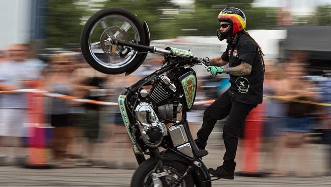 King Tony with Busted Knuckles Stunt Tour performs a standing wheelie ride as he moves past specators during the Sturgis Kentucky Bike Rally. July 14, 2017