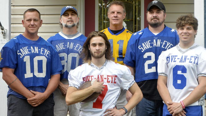 Members of the Glus extended family who played in the Save-An-Eye football game gather around Fairview High School graduate Micah Glus, 18, center, chosen for this year's game, now cancelled due to the COVID-19 pandemic. The others are, from back left,  Erik Glus, 41; Rob Glus, 41, Micah's dad; Greg Harayda, 58; Jason Brown, 40; and Jay Glus, 20, Micah's brother.