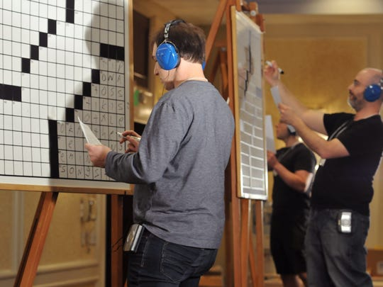Howard Barkin of Hillsborough tackles the downward right side of the championship puzzle during the three-way playoff  at the American Crossword Puzzle Tournament on April 3. Barkin beat the tournament's six-time champion, Dan Feyer, shown at Barkin's right.