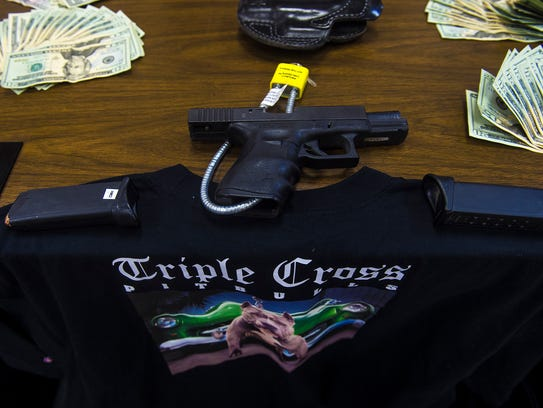 A gun, bills and a shirt displaying a Triple Cross