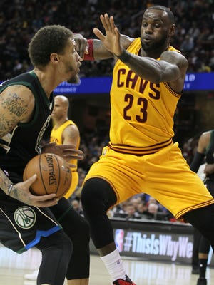 Michael Beasley is defended by LeBron James.