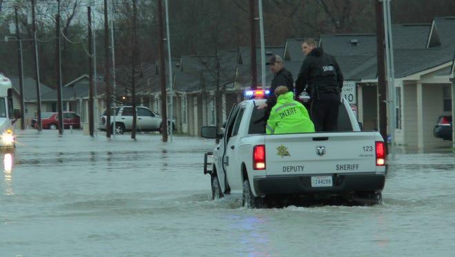 Ouachita Parish Sheriff's deputies provide assistance for residents evacuating Cotton Bayou Estates