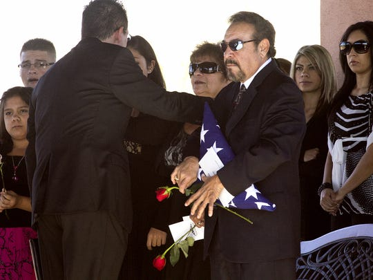 """Joe Atencio holda the flag from the coffin of his son, Ernest """"Marty"""" Atencio, during the funeral at the National Memorial Cemetery of Arizona in Phoenix on Jan. 4, 2012.   Ernest Atencio died after being stunned with a Taser at the Fourth Avenue jail."""
