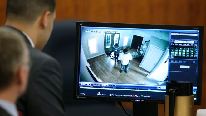 Former Patriots tight end Aaron Hernandez, top left, watches surveillance video displayed on at monitor during his murder trial.