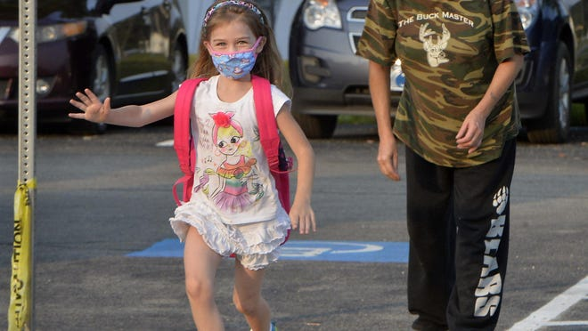 Six-year-old Bella Turben runs toward Union City Area Elementary School after being dropped off by her mother Judy Turben, 43, on Tuesday, the first day of school, in Union City. Staff, students and parents are adjusting to a new routine due to the COVID-19 coronavirus pandemic.