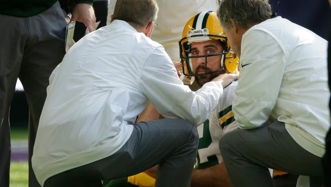 Green Bay Packers quarterback Aaron Rodgers (12) is tended to after being injured during the first quarter of their game against the Minnesota Vikings Sunday, October 5, 2017 at U.S. Bank Stadium in Minneapolis, Minn.