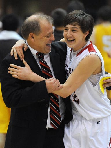 New Albany head coach Jim Shannon (left) celebrates with Isaac Hibbard (right) after the Bulldogs beat Evansville Central on Saturday during the first game of the Boy's Regional IHSAA Basketball Tourney at Seymour High School. Mar. 15, 2014