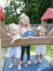 Genevieve, Lydia and Vera Taylor play in the backyard.
