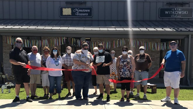 At the ribbon in front of Hometown Treasures are Port Jervis Councilman Tim Simmons, Councilwoman Maria Mann, owner Kelly DeStefano, Mayor Kelly B. Decker, Councilwoman-at-Large Lisa Randazzo and Councilman Regis Foster, flanked by crafters and vendors who sell their goods at the store.
