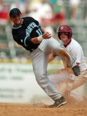 Coastal Carolina second baseman Tommy La Stella (11) steps awkwardly around sliding South Carolina base runner Adam Matthews (26) during a 2010 game.