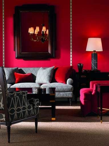 Red walls create a rich backdrop for furnishings designed
