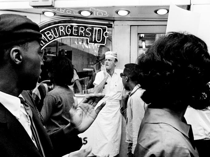 A Tic Toc Restaurant's employee keeps an eye on one of the five groups of 25 demonstrators paraded in front of the downtown store May 1, 1964. They marched in front of six segregated restaurants for two hours. Two of the marchers, John Lewis and Lewis Miller were slightly injured during a scuffle in front of the store.