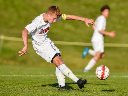 Champlain Valley Union's Nate Coffin boots the ball