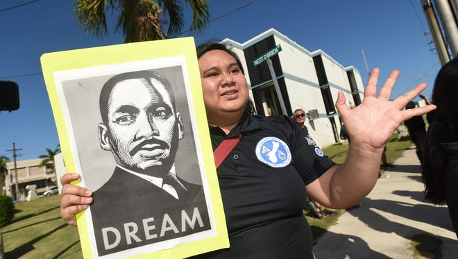 AmeriCorps Guam Homeland Security volunteer Norielyn O'Connor waves to passing vehicles duing a Martin Luther King Jr. Day wave in Hagåtña on Jan. 15, 2018.
