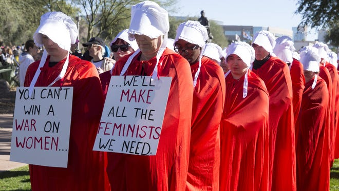 Handmaids' Resistance participate in the Women's March to the Polls 2018 at the Arizona State Capitol in Phoenix on Jan. 21, 2018. Handmaids' resistance wants to raise awareness to attacks on women's reproductive freedoms and access to life-saving healthcare.