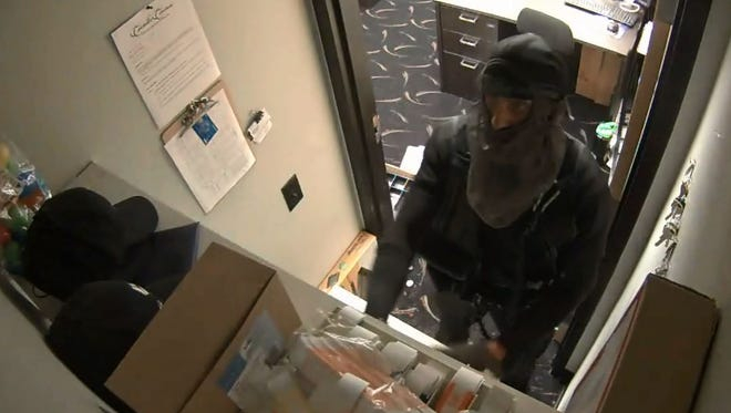 The suspect in the July 18 robbery of Manitowoc's Carmike Cinema is described as a white man with an athletic build, blond shaved head with a short mohawk, and tattoos on his right hand and wrist. Pictured is the suspect in a surveillance video still from the robbery.
