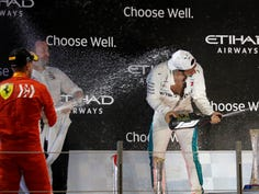 Mercedes driver Lewis Hamilton of Britain cheers with marshals, followed by US actor Will Smith, prior to the start of the Emirates Formula One Grand Prix at the Yas Marina racetrack in Abu Dhabi, United Arab Emirates, Sunday, Nov. 25, 2018.(AP Photo/Kamran Jebreili)