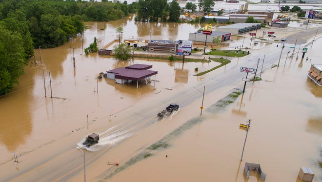 A military vehicle, left, and a truck pulling a boat pass in front of flooded businesses under water along U.S. 67 Wednesday, May 3, 2017,  in the heavily flooded East Pocahontas, Ark.  Downpours that dumped up to a foot of rain in parts of the nation's midsection last weekend led to the sudden surge of water.