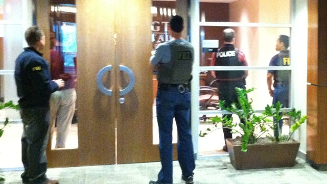 FBI agents and police guard the front of Remington Capital's Scottsdale office, which was raided in March 2011.