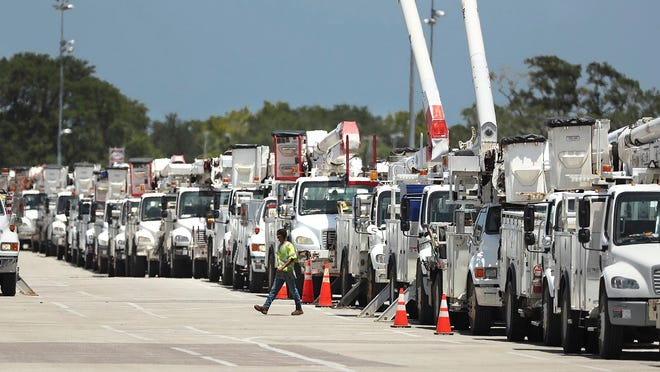 Dozens of utility trucks are lined up to be processed by Florida Power & Light at Daytona International Speedway on Saturday in preparation for Hurricane Isaias, which weakened to a tropical storm as it churned toward the Florida coast Sunday.
