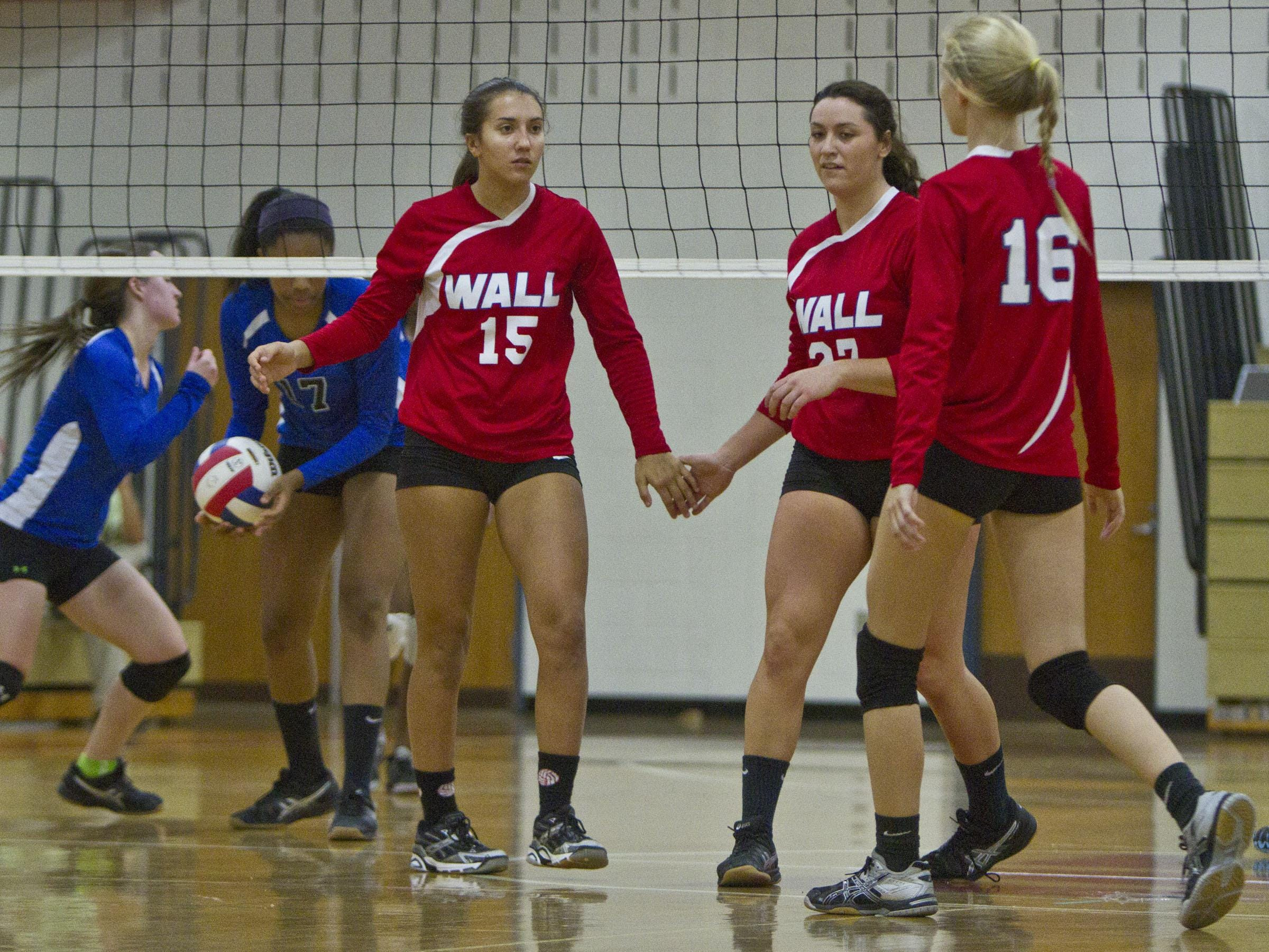 Wall's Jess Stansfield (15), Colleen Brennan (27) and Kaitlyn Pepe celebrate a point. NJSIAA volleyball match between Wall and West Windsor Plainsboro North. Wall Township, NJ Wednesday, November 4, 2015 @dhoodhood