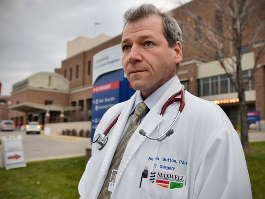 Chris Sutton, 45, is a physician's assistant in the CentraCare Health who has survived three bouts with cancer and another with heart disease. He was photographed after work Nov. 4 outside St. Cloud Hospital where he works. Sutton credits his own research and advocacy with finding the treatments to allow him to survive despite unfavorable odds.