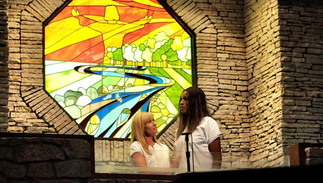 Stefanie Jeffers (left), co-founder of Stripped Free, baptizes Jenea in May 2014 at Mount Pleasant Christian Church in Greenwood. Jenea rejoined the church after she quit dancing in an Indianapolis strip club.