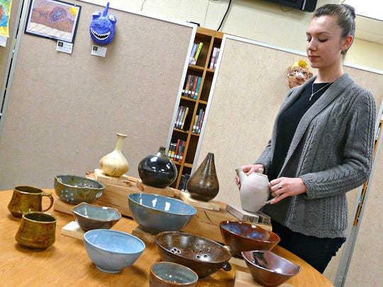 Ceramicist Kait Prickett, a senior, arranges her creations