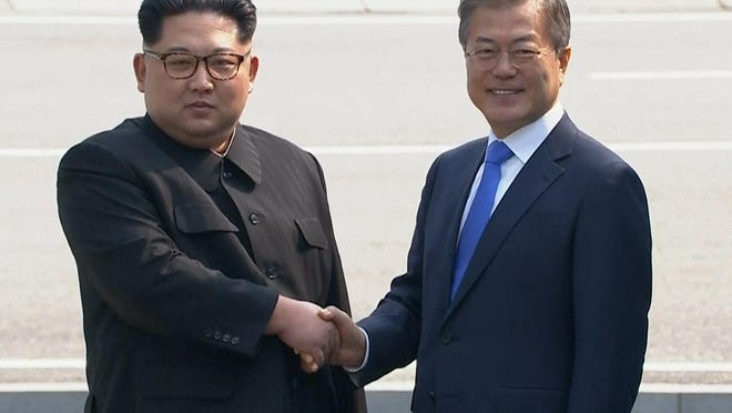 North Korean leader Kim Jong Un, left, shakes hands with South Korean President Moon Jae-in as Kim crossed the border into South Korea on Friday.