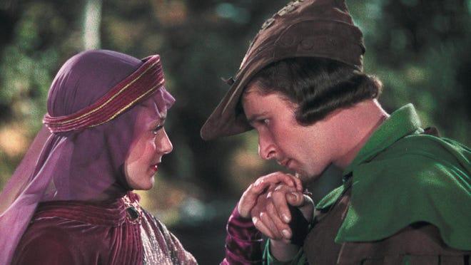 """Robin Hood (Errol Flynn) kisses the hand of Lady Marian Fitzwalter (Olivia de Havilland) in the 1938 version of """"The Adventures of Robin Hood."""""""