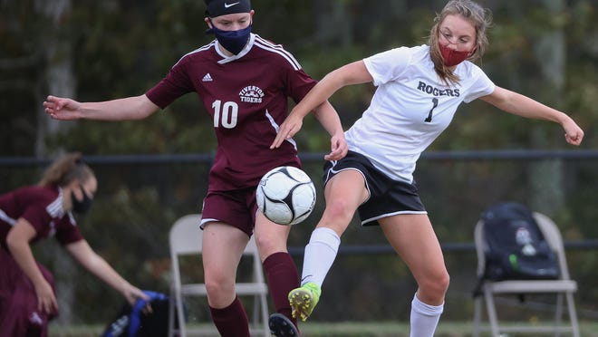 Emma Leach, right, of Rogers battles for possession of the ball with Tiverton's Maeve Banal during Saturday's game. Players this season are required to wear masks during the contest.