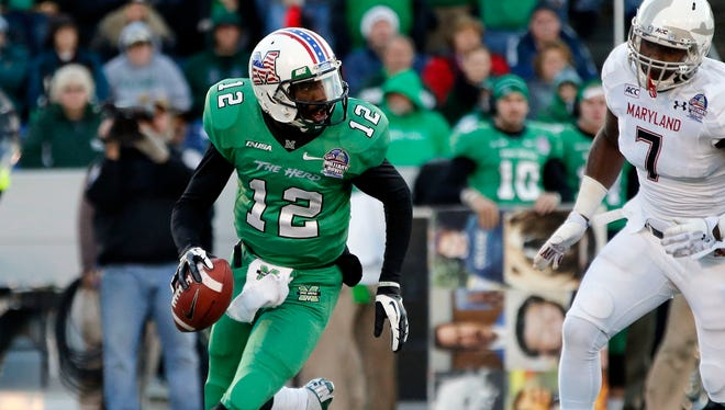 Marshall quarterback Rakeem Cato (12) rolls out as Maryland Terrapins linebacker Yannick Ngakoue (7) chases in the second quarter during the 2013 Military Bowl at Navy Marine Corps Memorial Stadium.
