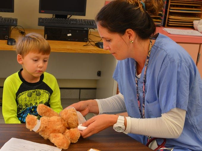 Physician's assistant Megan Daniels shows Maddox Brown