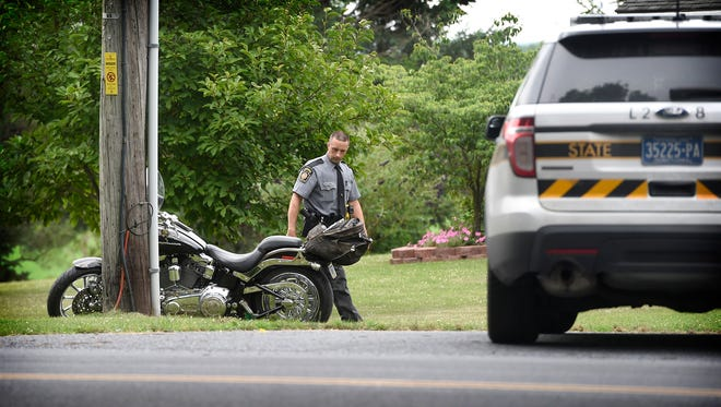 A state trooper looks over a motorcycle after a crash at 6:21 p.m. Sunday, July 3, 2016, on Houtztown Road in Jackson Township. The driver of the motorcycle was injured and taken to a hospital.