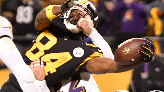 Pittsburgh Steelers wide receiver Antonio Brown (84) reaches the ball across the goal line to score the game winning touchdown as Baltimore Ravens strong safety Eric Weddle (32) defends in the fourth quarter.