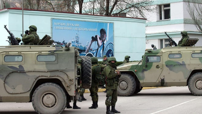 Unidentified armed individuals with armored vehicles block the base of the Ukrainian border guard service in Sevastopol on Saturday.