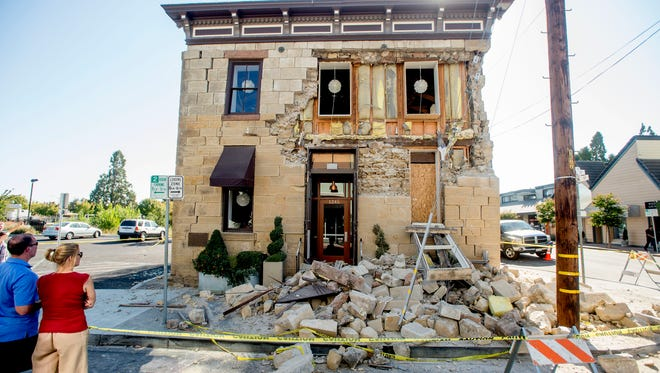 Pedestrians stop to examine a crumbling facade at the Vintner's Collective tasting room in Napa, Calif., after an earthquake Aug. 24, 2014.