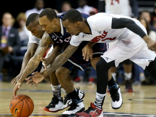 U of L's Chris Jones, #3, left, and Russ Smith, #2, right, squeeze UConn's Ryan Boatright, #11, as they try to take the ball from him during the AAC Tournament Championship at the FedEx Forum in Memphis, Tn. Mar. 15, 2014