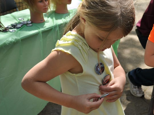 """Emma Wilkerson collects pins Saturday morning at the Alexandria Zoo's """"Why Animals Kick Butts"""" scavenger hunt. A map showed kids 10 different animal stations throughout the zoo. Once kids collected all their pins, they received a prize bag."""