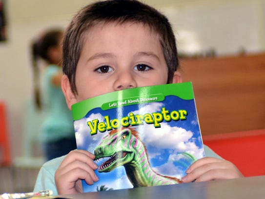 Four-year-old Jude Armijo enjoys reading about dinosaurs