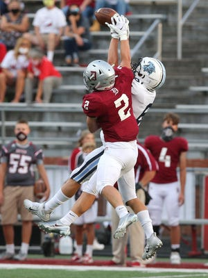Jacob Hostetler (2) of Dover breaks up a pass intended for Zack Seaman (6) of Louisville during their game at Dover on Thursday, August 27, 2020.