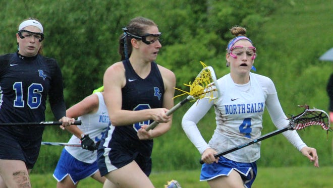 Putnam Valley's Jackie Phillips cradles the ball while guarded by North Salem's Lydia Werlau. Putnam Valley won 8-7 in the Class D semifinals at Volunteers Park May 22, 2017.