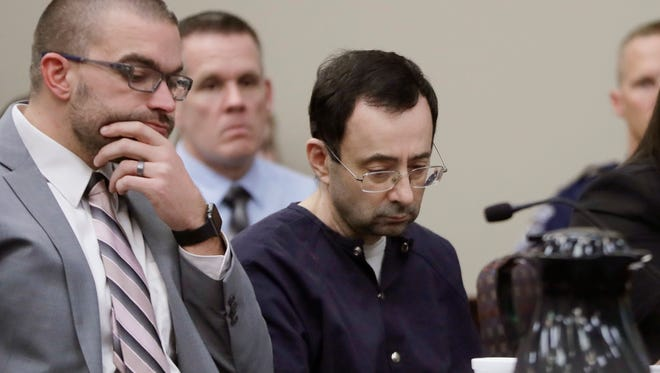 """Larry Nassar sits with attorney Matt Newburg during his sentencing hearing Wednesday in Lansing, Michigan. The former sports doctor who admitted molesting some of the nation's top gymnasts for years was sentenced Wednesday to 40 to 175 years in prison as the judge declared: """"I just signed your death warrant.""""  The sentence capped a remarkable seven-day hearing in which scores of Nassar's victims were able to confront him face to face in the Michigan courtroom."""