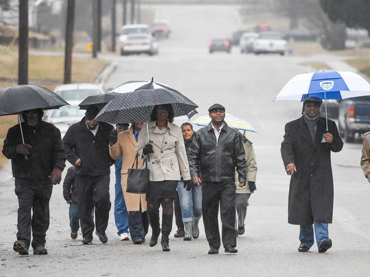 Walking in a drizzling rain, participants in a Martin Luther King march make their way along Plum Street in Henderson as they make their way to the New Race Creek Baptist Church for a service Sunday, January 15, 2017.