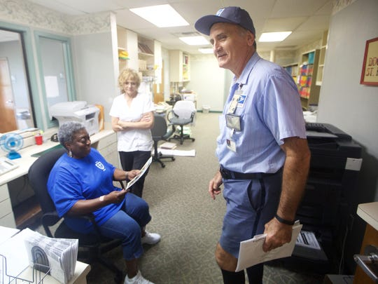 """Tim Kelly jokes with some of his customers, including Hattie Blackshear, from left, and Janine Gray on the last week covering a postal route he has worked in Tallahassee since 1983. """"It's a show everytime he comes in,"""" said Gray about Kelly's impromptu comedy. """"He's funny, he entertains and he's sweet…and he does his job!"""""""