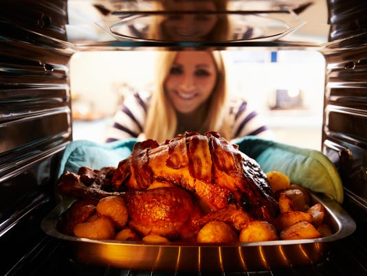 Woman Taking Roast Turkey Out Of The Oven