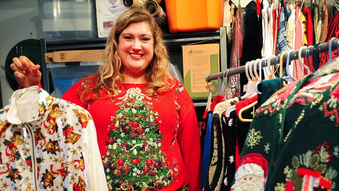 Rachel Duncan holds a Christmas track suit, one of the many tasteless holiday treasures in her collection. She started collecting ugly holiday clothing, because her grandma kept giving her sweaters on Christmas.